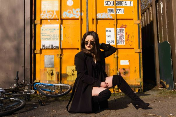 Model knelt in front a yellow container