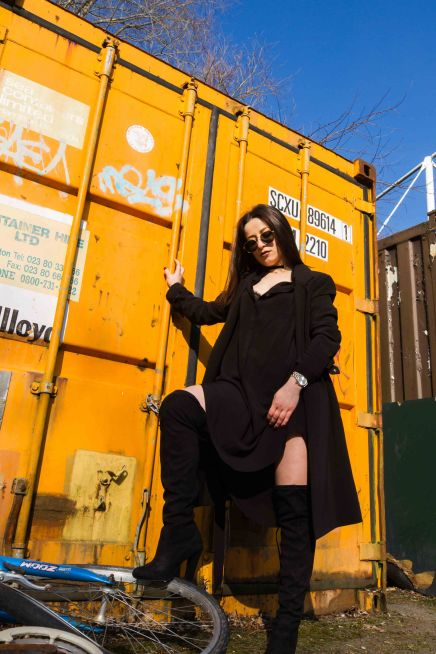 Wide angle portrait of model all in black against a yellow container