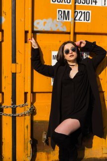 Portrait of model stood in front of yellow storage container