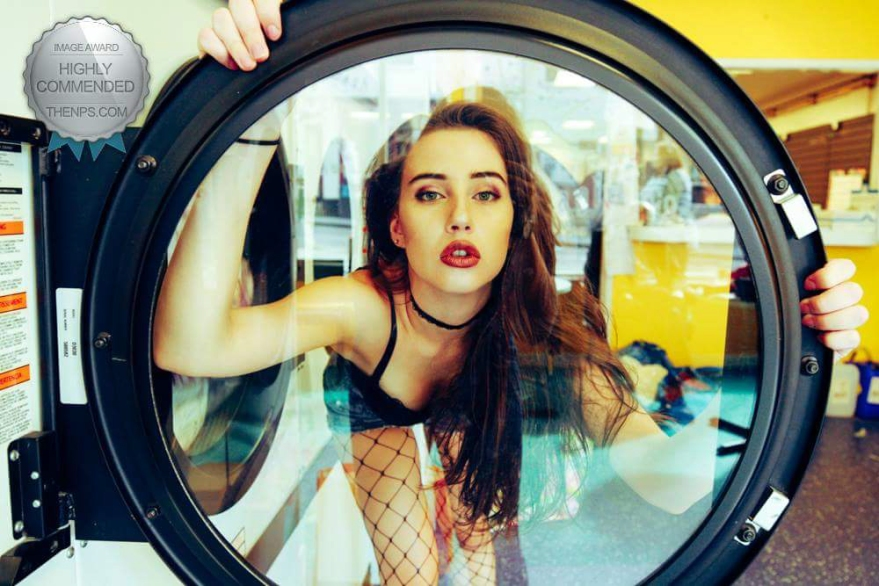 Highly commended award for laundry day portrait of model behind the washing machine window