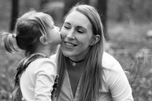 black and white mother daughter portrait with daughter kissing