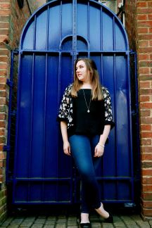 Female full body portrait in front of a bright blue gate