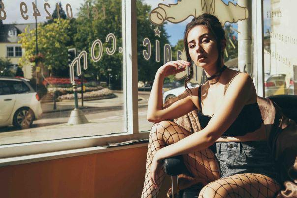 fed up model sat in front of a big window in vintage tones