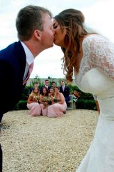 Bride and Groom kissing with group of friends underneath