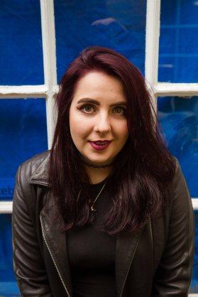 Smiling natural light portrait of model infront of blue window