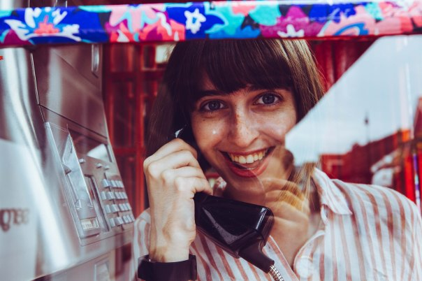 Contact image with a woman holding a phone in a telephone box
