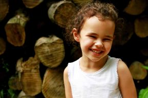 Child portrait in front of a stack of logs