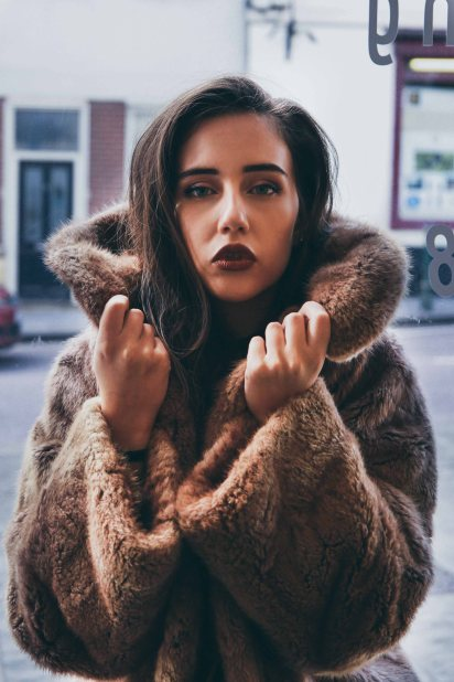 Close up portrait with brown haired model in a fur coat