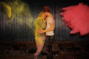 Couple kissing whilst red and yellow powder paint are thrown