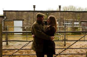 Couple cuddling in a barn