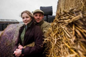 On the farm couple portrait cuddling next to the hay