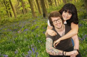 Couple portrait hugging in the bluebell woods for an engagement photo shoot