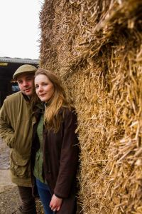 Country couple portrait with farmer and wife cuddling and hay to the right