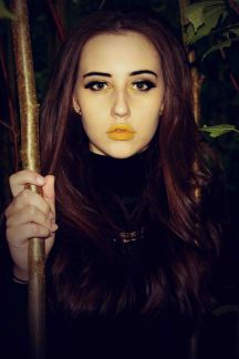 Close up portrait of model with yellow lipstick holding a branch