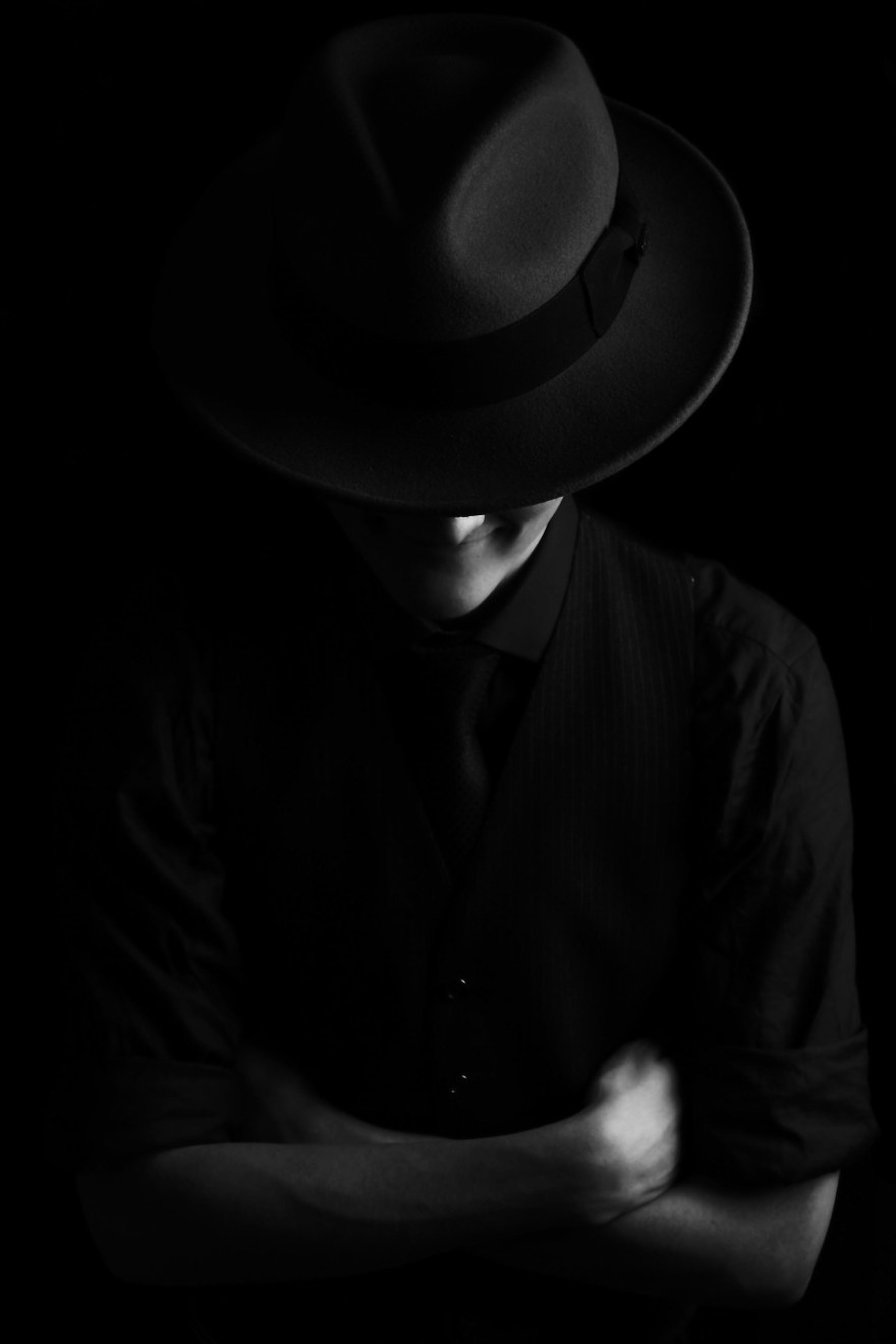 Low key edge lighting black and white portrait of male fedora