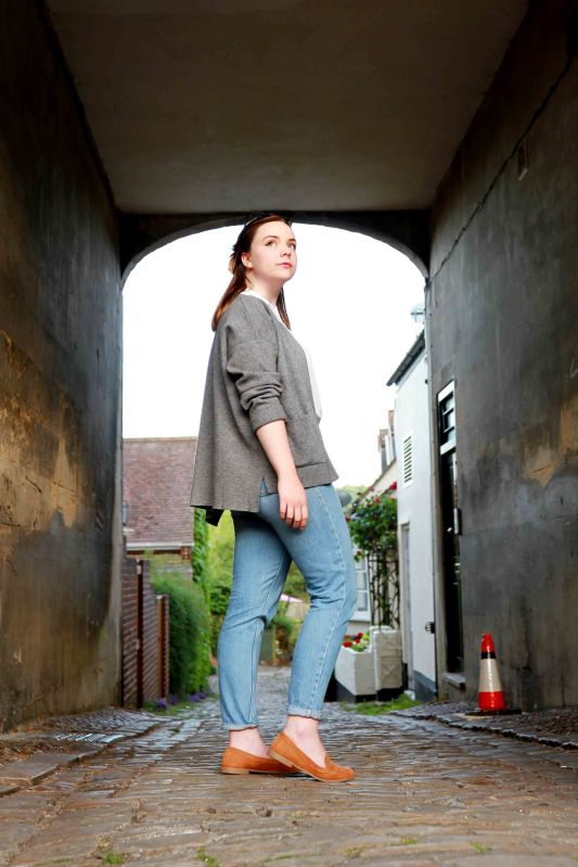 Lifestyle full length portrait of hipster woman walking through a model