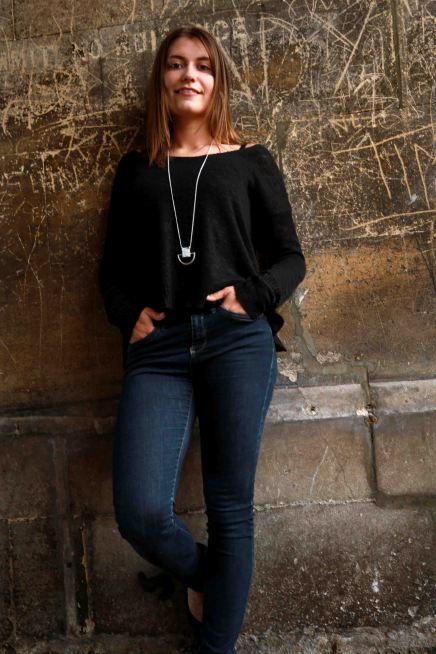 Urban portrait of female model leaning against an urban wall