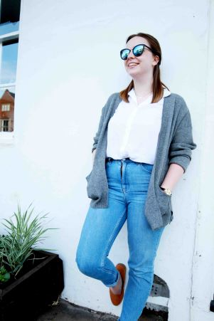 Blogger lifestlye portrait of model in highwaisted jeans, leaning against a wall wearing sunglasses