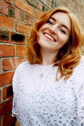 Laughing portrait of ginger model in front of a brick wall