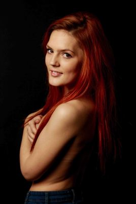 nude portrait of red haired model with low key studio lighting