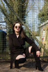 Urban portrait of model in front of fence