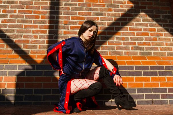 Model knelt in front of brick wall with red popper tracksuit and fishnets