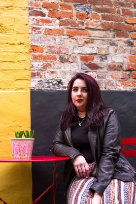 Lifestyle portrait of purple haired model sat down in front of a yellow wall