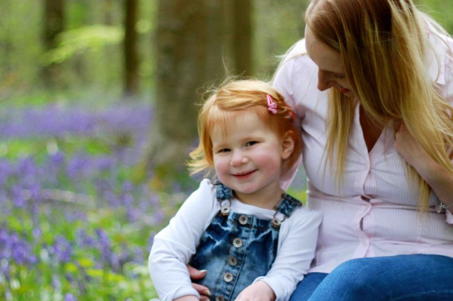 Mother hugging daughter in a field of blue bells