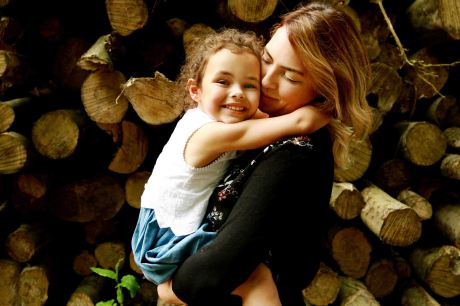 Mother and daughter hugging with a stack of logs in the background