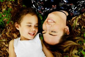 Mother and daughter laughing whilst lying on the grass