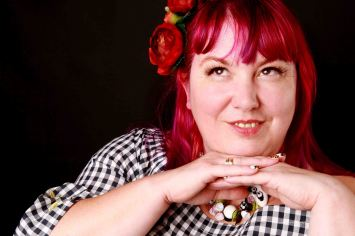 Plus size model portrait with pink hair and panda necklace
