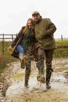Couple photoshoot in the rain with them splashing in a puddle