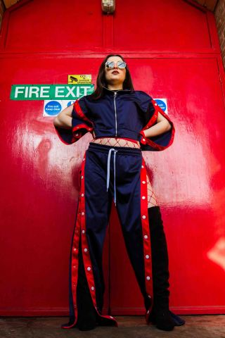Red and blue fashion editorial portrait with blue tracksuit and red back drop