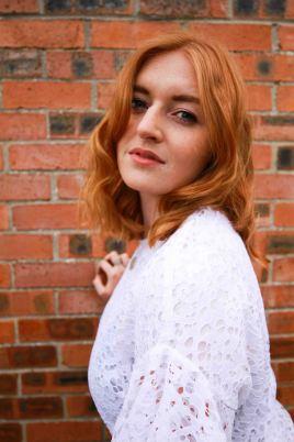 Ginger model portrait with brick backdrop