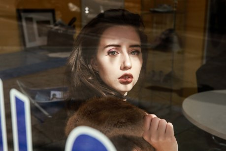 Brown haired model shot through reflective glass