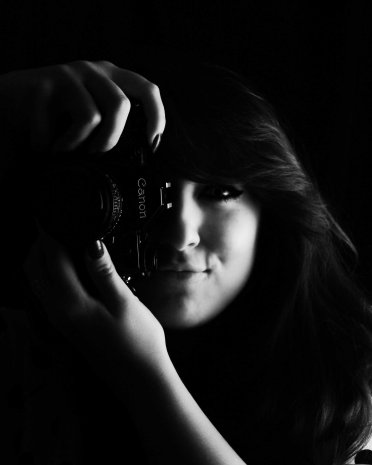 Low key black and white self portrait in studio holding camera