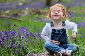 Laughing child portrait in a field of bluebells