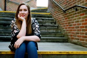 Lifestyle portrait of woman sat on stairs
