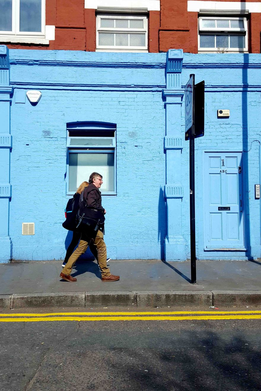 Street photography with people walking in front of a blue house