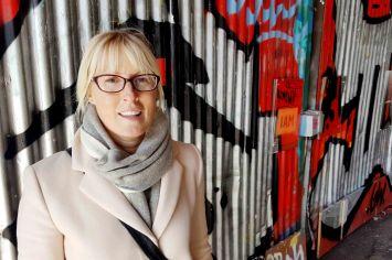 Street portrait of woman against graffiti wall