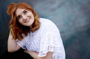 Ginger haired model laughing with grey background