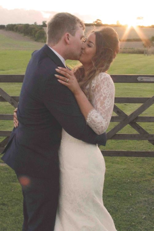 wedding sunset portrait with bride and groom kissing