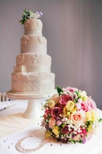 Tiered wedding cake with flowers in front