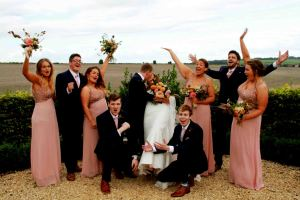bride and groom kissing while friends cheer