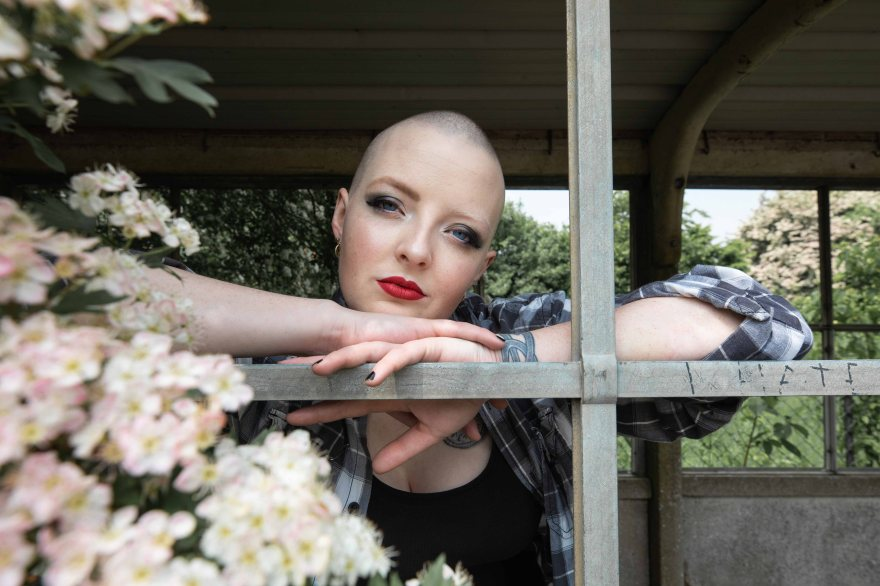Bald model framed by wooden windows and blossoms
