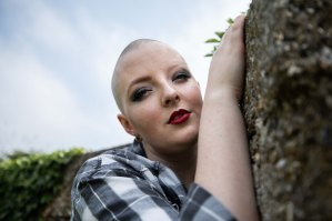Close up portrait of bald alternative model holding a wall