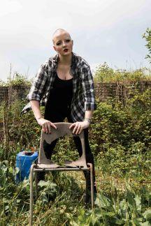 Full length portrait of bald alternative model holding onto broken chair