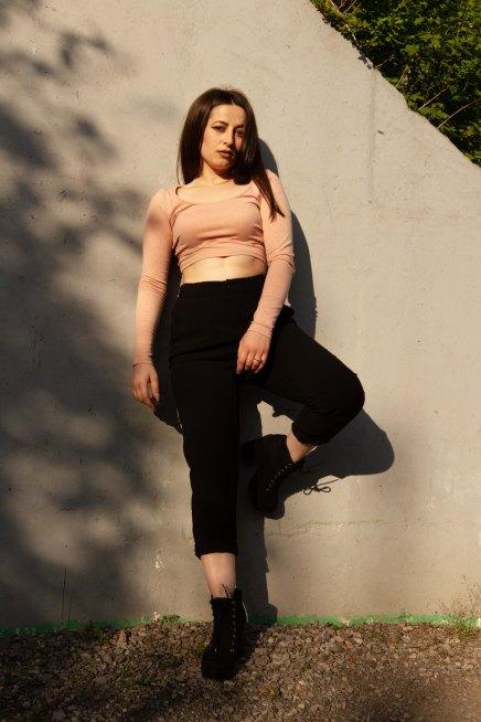 Full length portrait of model posing against white wall