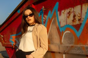 Model leaning against graffiti skip with sunglasses on