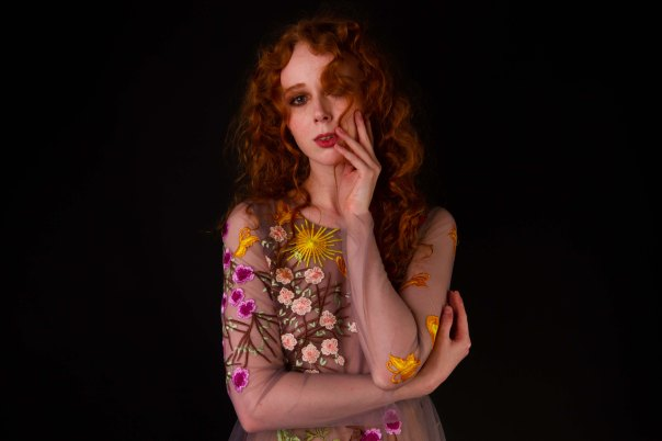 Red haired model holding her face in a floral dress